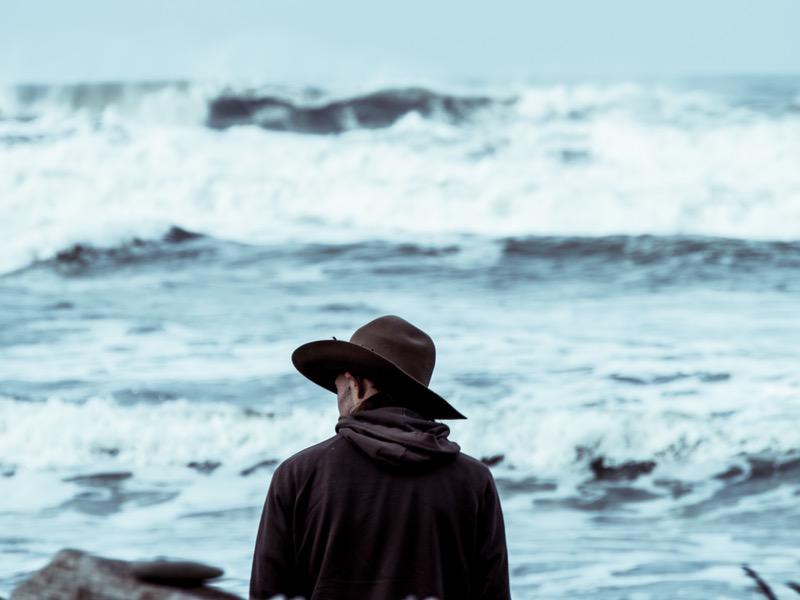 Black Hat SEO - Cowboy mit schwarzem Hut sitzt vor Surferwellen -