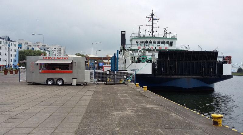 Waffelbude neben einem Frachtschiff am Hafen in Swinemünde