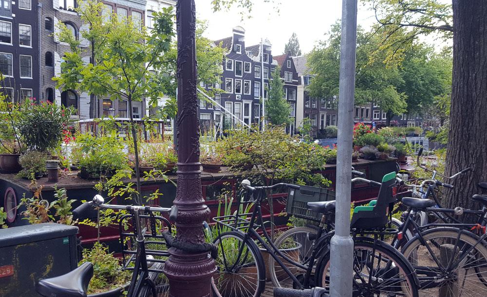 Fahrräder und ein Hausboot an einer Gracht in Amsterdam