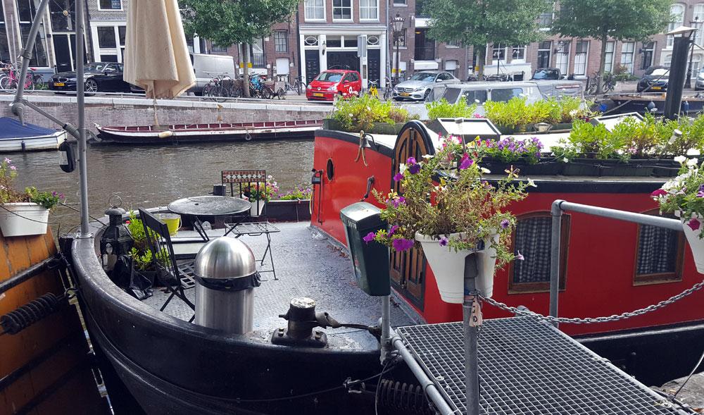 schön bepflanztes Hausboot an einer Gracht in Amsterdam