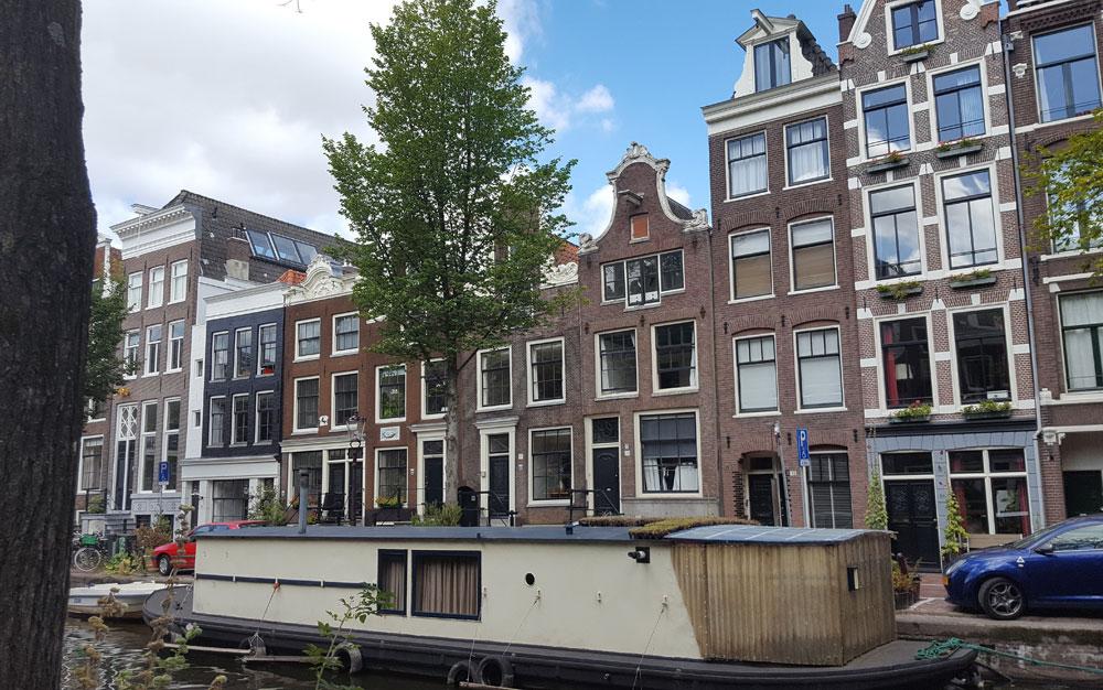noch ein Hausboot vor einer typischen Grachtenhhausfassade in Amsterdam