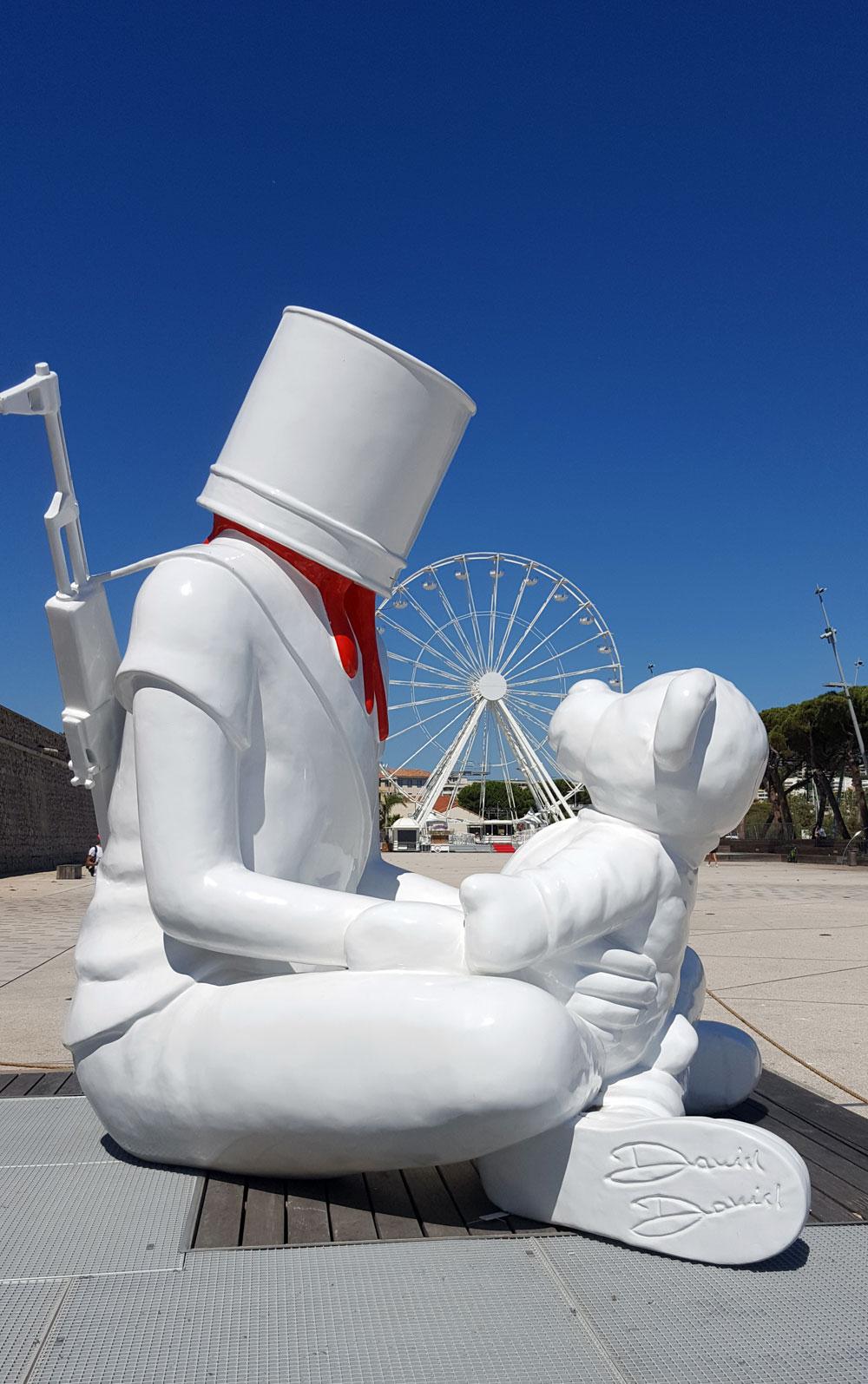 Skulptur von David David mit Gewehr und Teddybär vor dem Riesenrad
