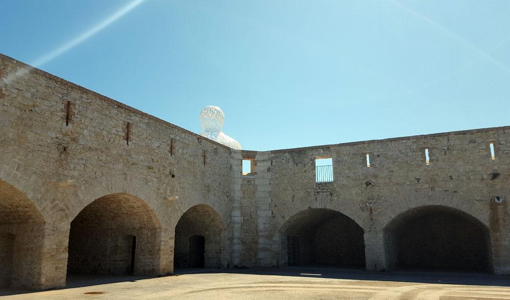 """Die Festungsmauer vor der Skulptur """"Le Nomade"""""""