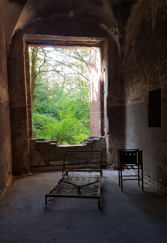 Ein altes Metall-Bettgestell vor einem Fensterdurchbruch