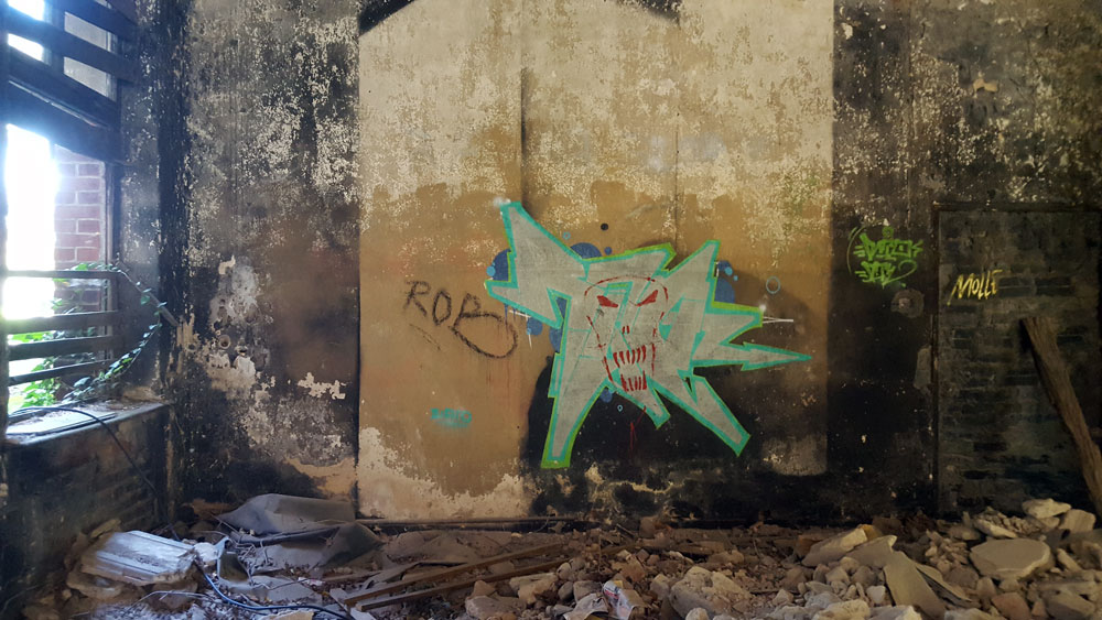 Graffiti an einer Wand hinter Bauschutt