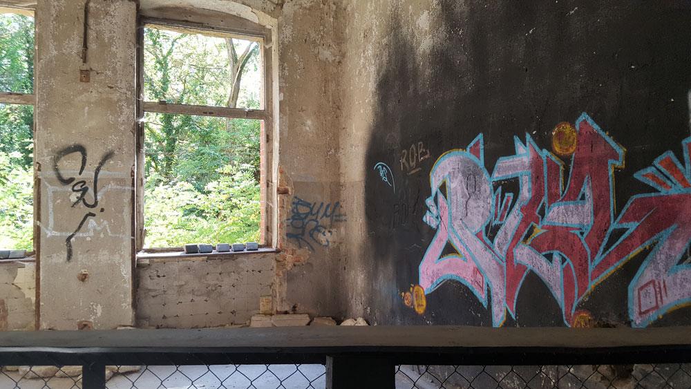 Buntes Graffiti an einer verkohlten Zimmerwand