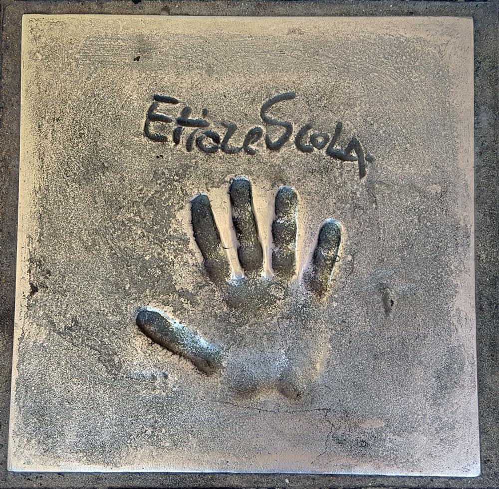 """Handabdruck von <a href=""""https://de.wikipedia.org/wiki/Ettore_Scola"""" target=""""_blank"""" rel=""""noopener"""">Ettore Scola</a> - ein italienischer Filmregisseur und Drehbuchautor, geboren am 10. Mai 1931 und gestorben am 19. Januar 2016"""