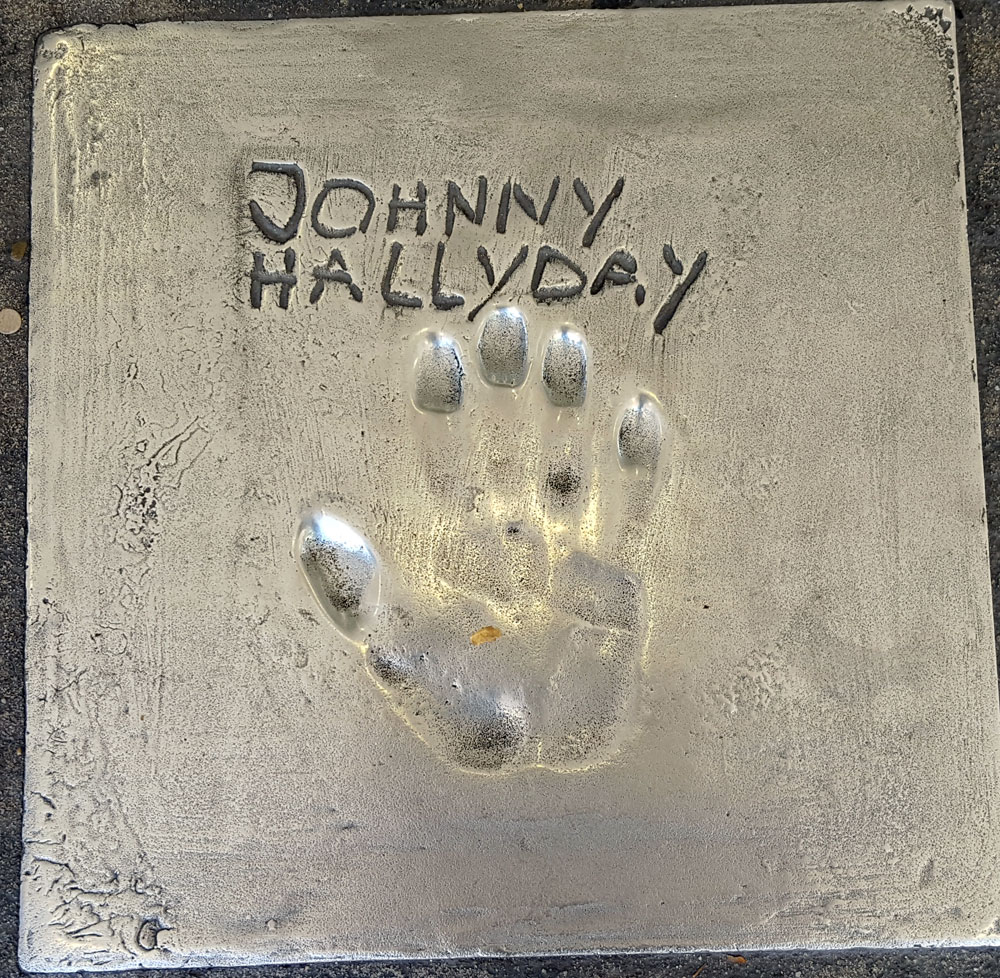 """Handabdruck von <a href=""""https://de.wikipedia.org/wiki/Johnny_Hallyday"""" target=""""_blank"""" rel=""""noopener"""">Johnny Hallyday</a> - ein französischer Sänger, Songwriter und Schauspieler, geboren am 15. Juni 1943 und gestorben am 5. Dezember 2017"""