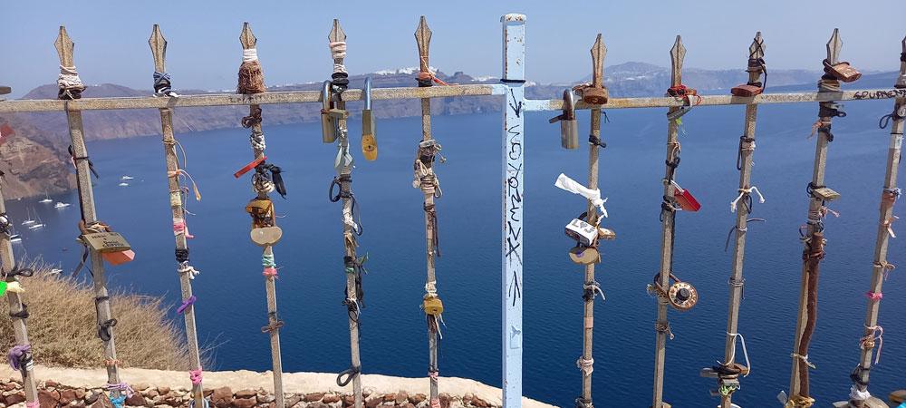 Liebesschlösser an einem Geländer auf der Ruine des Kastells Argyri in Oia