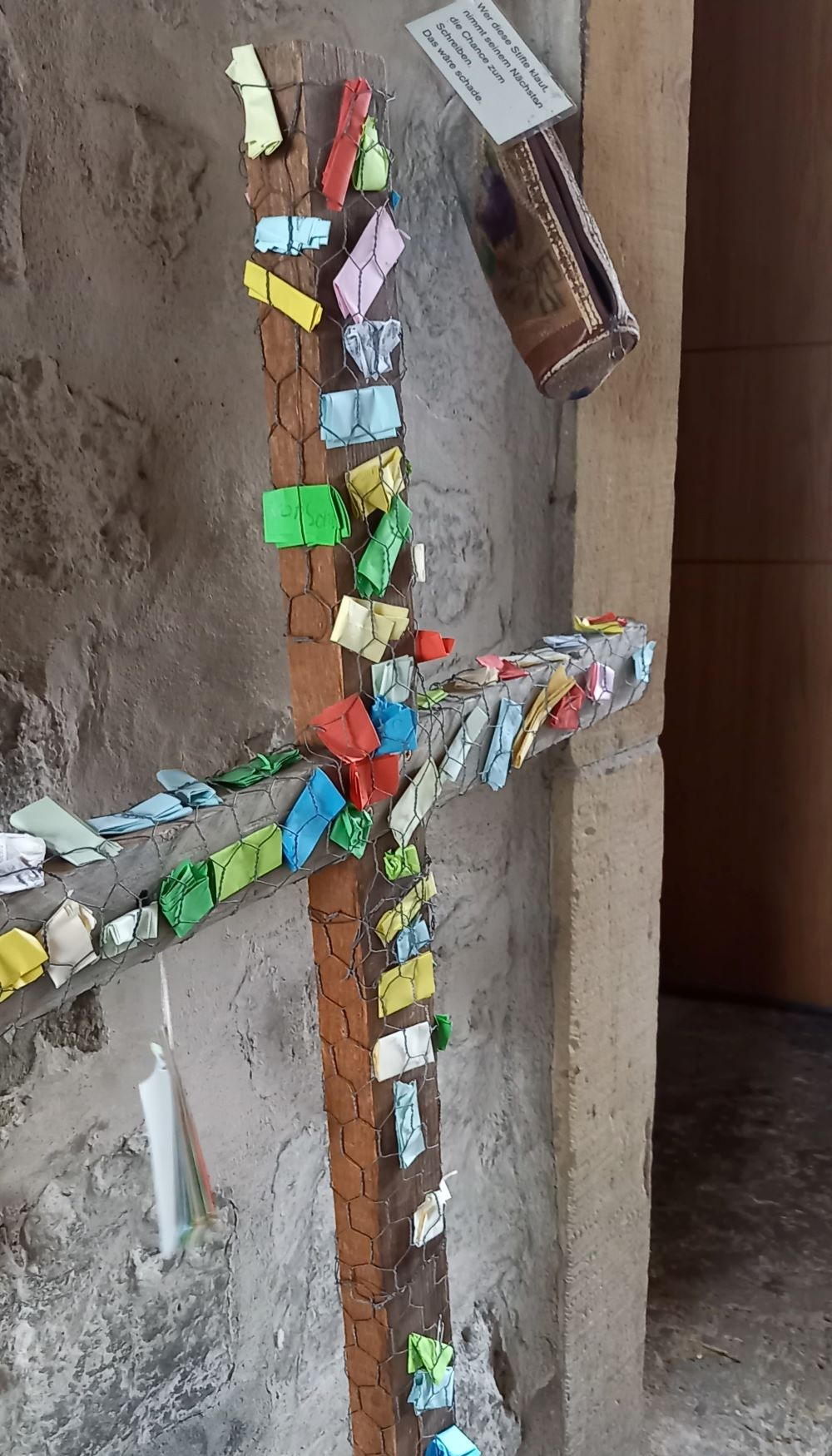 Kreuz mit bunten Wunschzetteln am Eingang der Erfurter Ägidienkirche