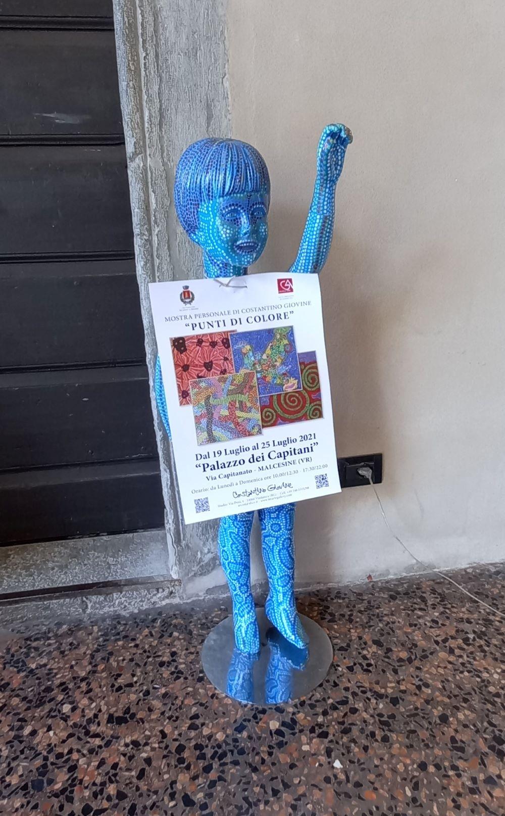 """Blaue Mosaik-Figur mit Plakat """"punti di colore"""" im Ergeschoss des Palastes"""